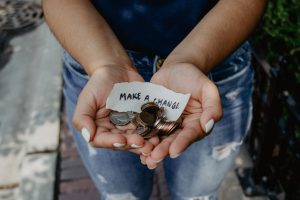 hand holding loose change and handwritten make a change note